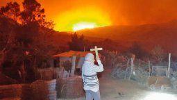 Delfina Urquiza vive desde hace 50 años en un puesto ubicado en Tres Cerros. Su imagen con un crucifijo en alto implorando para que el fuego no llegue a su casa se viralizó.