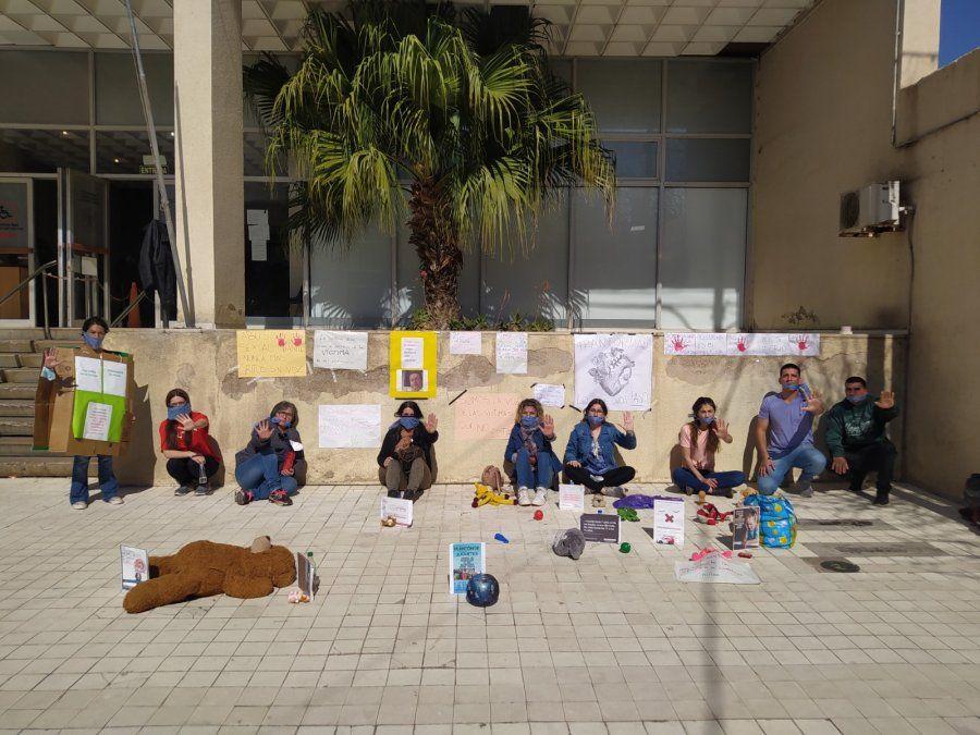 Integrantes de la organización junto a la intervención con juguetes que realizaron en la vereda del edificio de tribunales.