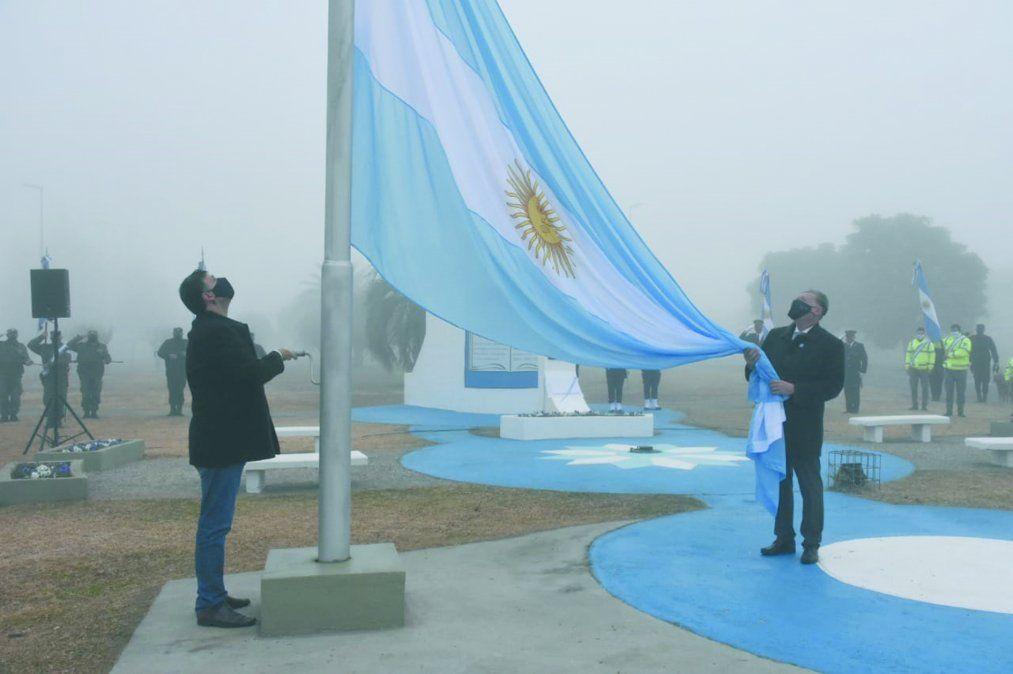 Rosso y De Falco izando la insignia patria mientras de fondo fue interperatada a capella la canción Aurora.