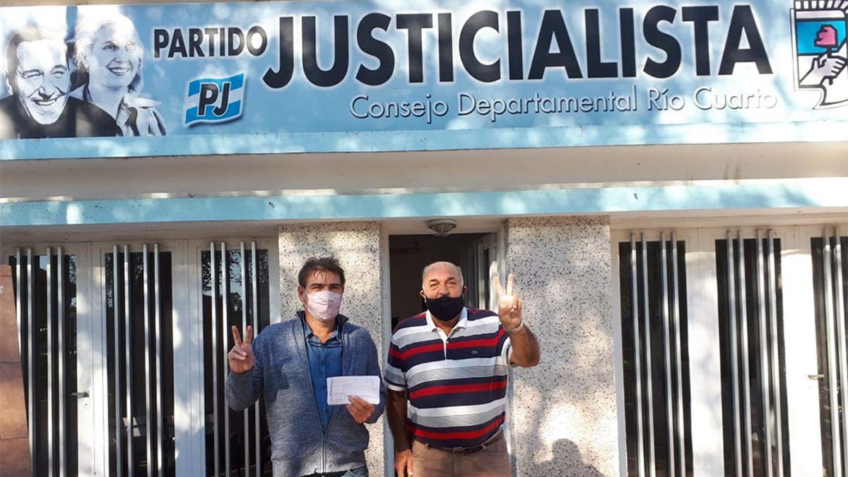 Vaca Narvaja y Abraham en la sede del PJ con los dos dedos en V de la victoria y la ficha de afiliación al partido.